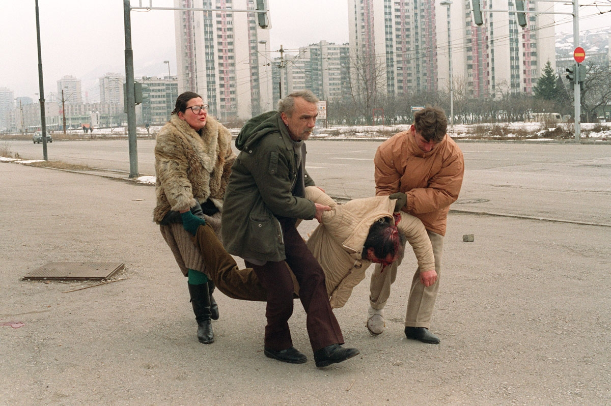 People carry away 08 March 1993 in Sarajevo a man wounded by a shell which fell near the television station during the Serb forces shelling of the Bosnia-Herzegovina capital.