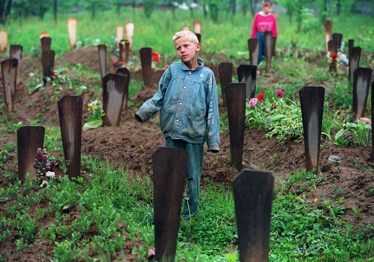 A Bosnian boy stands 06 May 1994 among the 200 graves in the Muslim cemetery in Ograndjenavac, Bosnia.  On the seventh of May the Bosnian Croats and the Bosnian Muslims began a new series of peace talks at the US Embassy in Vienna.