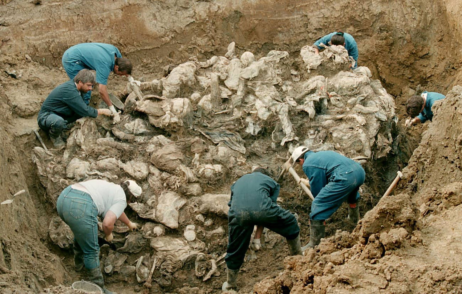 Forensic experts from the International war crimes tribunal in the Hague works on a pile of partly decomposed bodies, 24 July 1996 found in a mass grave in the village of Pilica some 300 km northeast of Sarajevo. The victims in the human sculpture is said