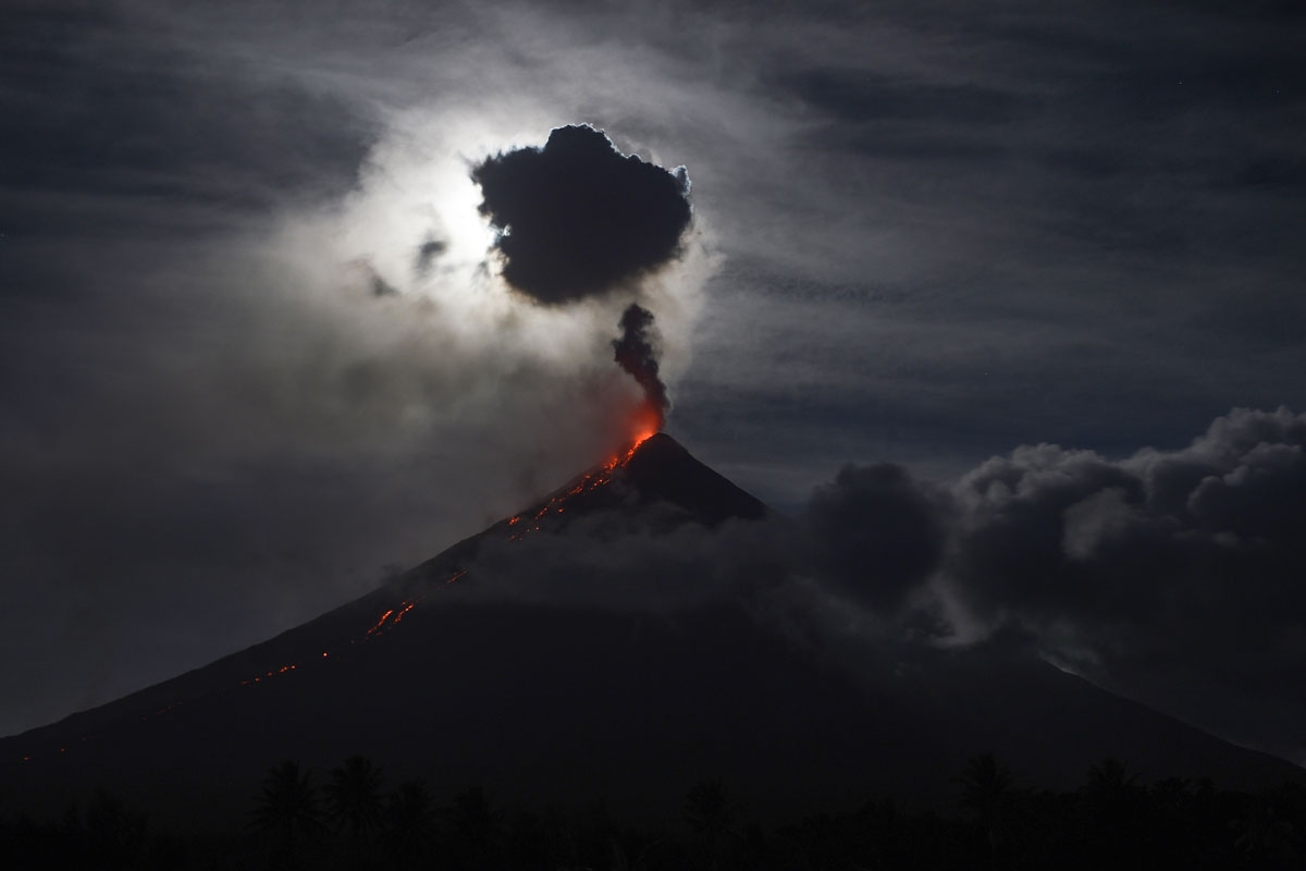 The 'super blue blood moon' obscured by clouds illuminates Mayon volcano as it spews ash near Legazpi City, Albay province, early on February 1, 2018.