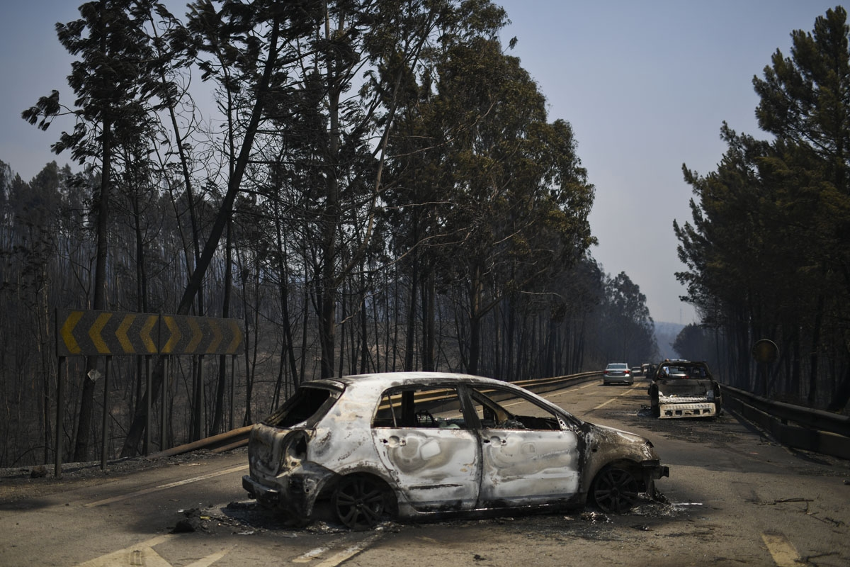 A picture taken on June 18, 2017 shows burnt cars on a road after a wildfire in Figueiro dos Vinhos.