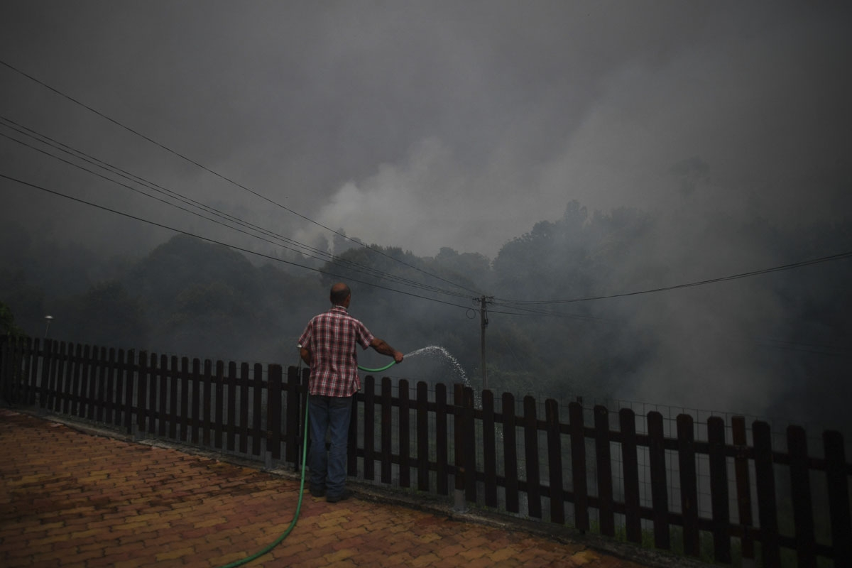 A resident of the village of Trespostos uses a hose as he tries to extinguish a wildfire surrounding their houses, in Figueiro dos Vinhos on June 18, 2017.