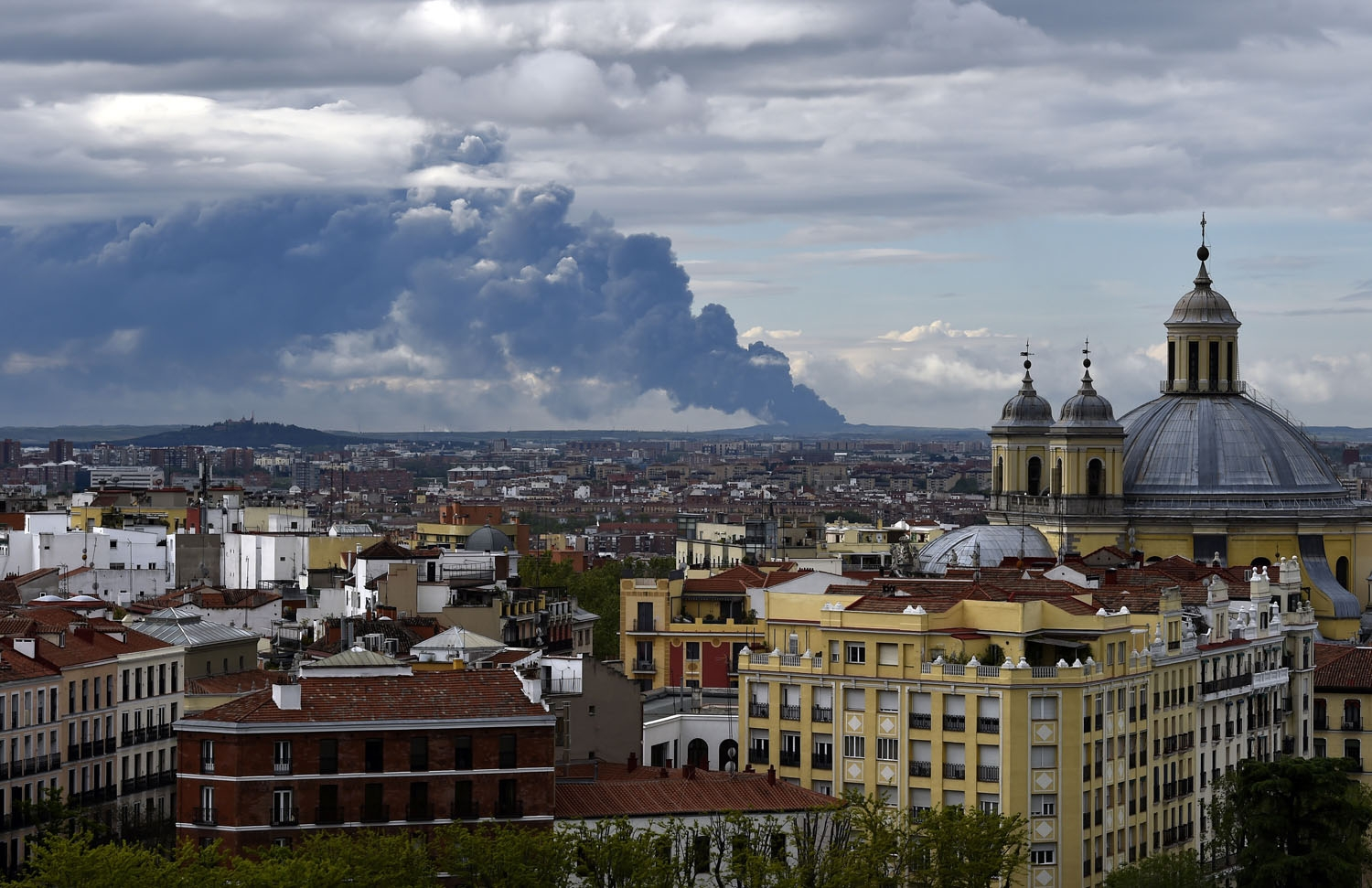 Picture taken from the Almudena cathedral in Madrid shows a huge smoke column caused by a fire in an uncontrolled dump near the town of Sesena, on May 13, 2016