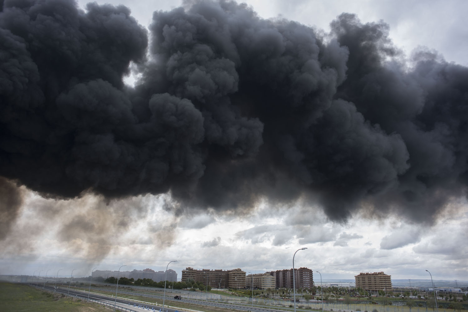Black clouds of smoke are produced by tyres burning in an uncontrolled dump near the town of Sesena, after a fire brokeout early on May 13, 2016