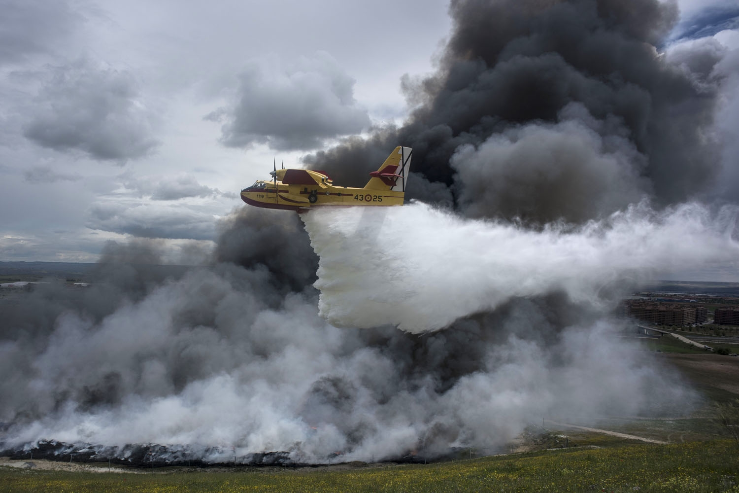 A seaplane discharges water over the tyres burning in an uncontrolled dump near the town of Sesena, after a fire brokeout early on May 13, 2016