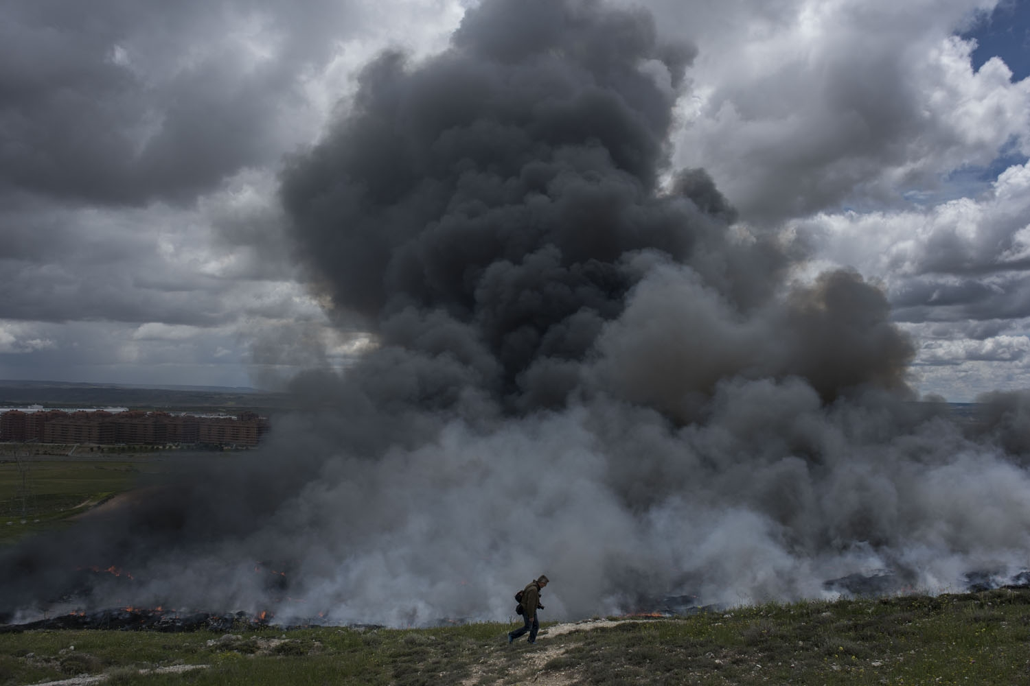 A man walks past a pile of tyres burning in an uncontrolled dump near the town of Sesena, after a fire brokeout early on May 13, 2016