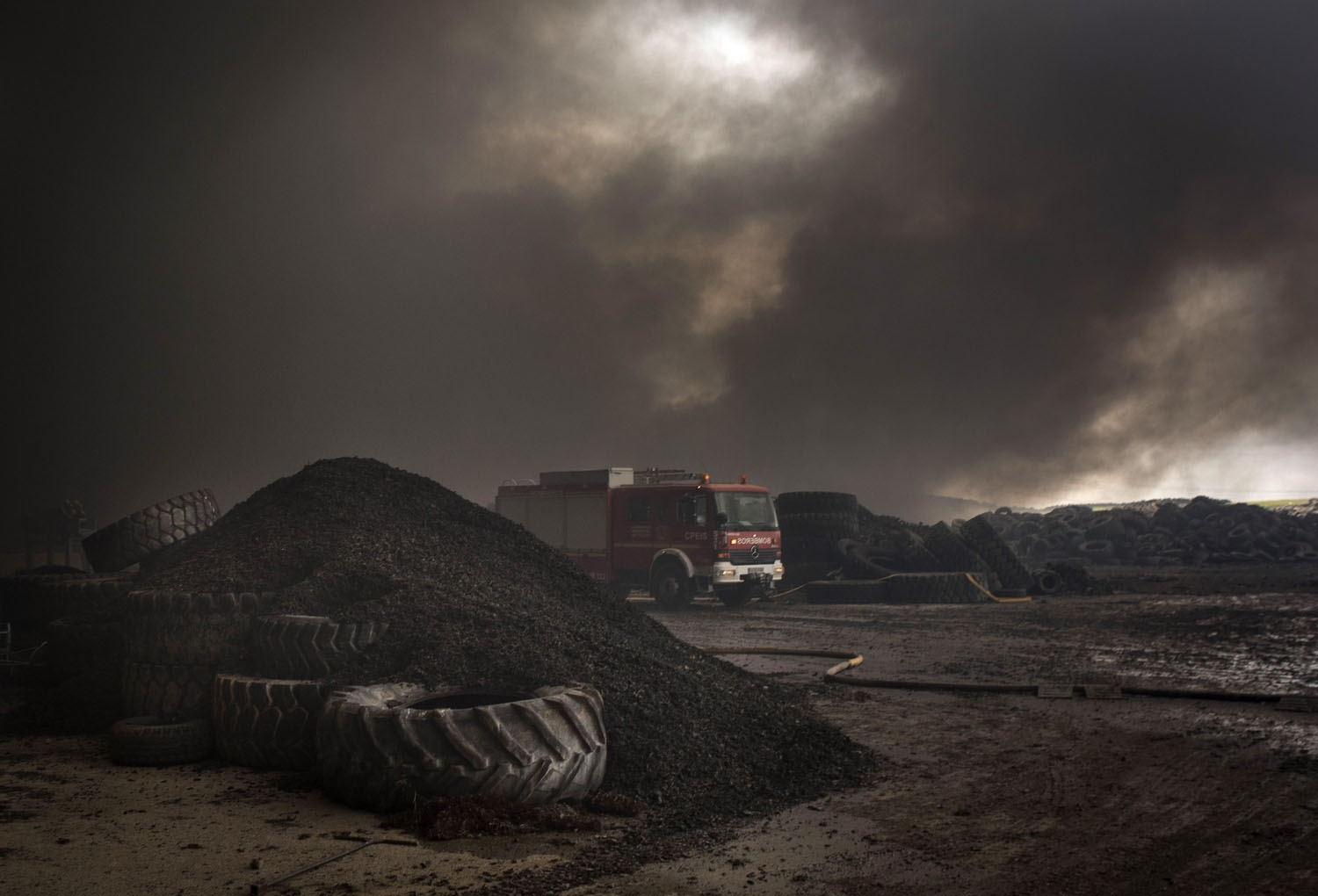 Clouds of dark smoke cover the sky as a fire truck drives among piles of tyres in an uncontrolled dump near the town of Sesena, after a fire brokeout early on May 13, 2016