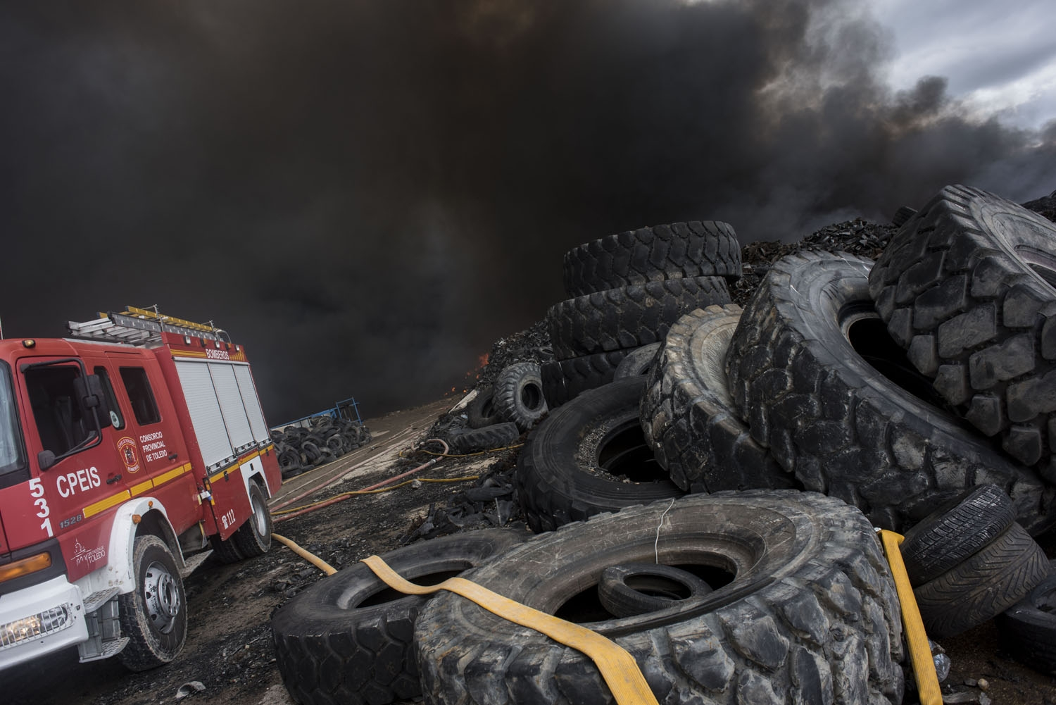 Clouds of dark smoke cover the sky as a fire truck works among piles of tyres in an uncontrolled dump near the town of Sesena, after a fire brokeout early on May 13, 2016