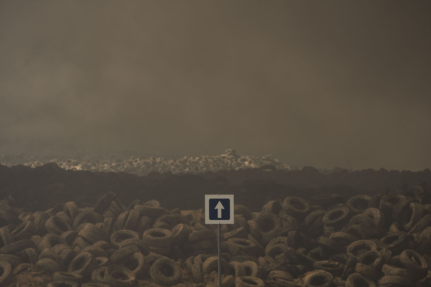 Tyres burn in an uncontrolled dump near the town of Sesena, after a fire brokeout early on May 13, 201