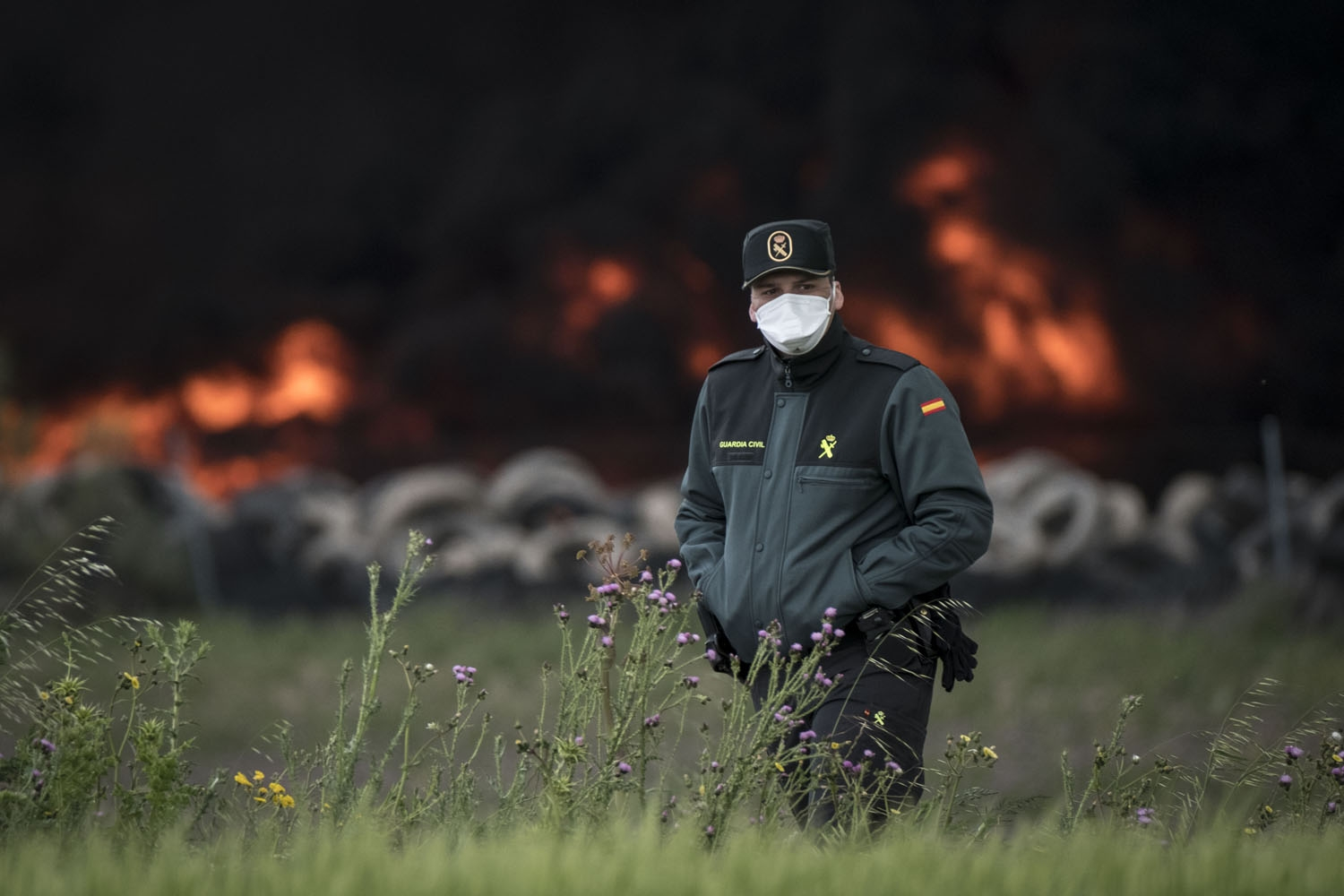 A civil guard with a mask walks past a pile of tyres burning in an uncontrolled dump near the town of Sesena, after a fire brokeout early on May 13, 2016