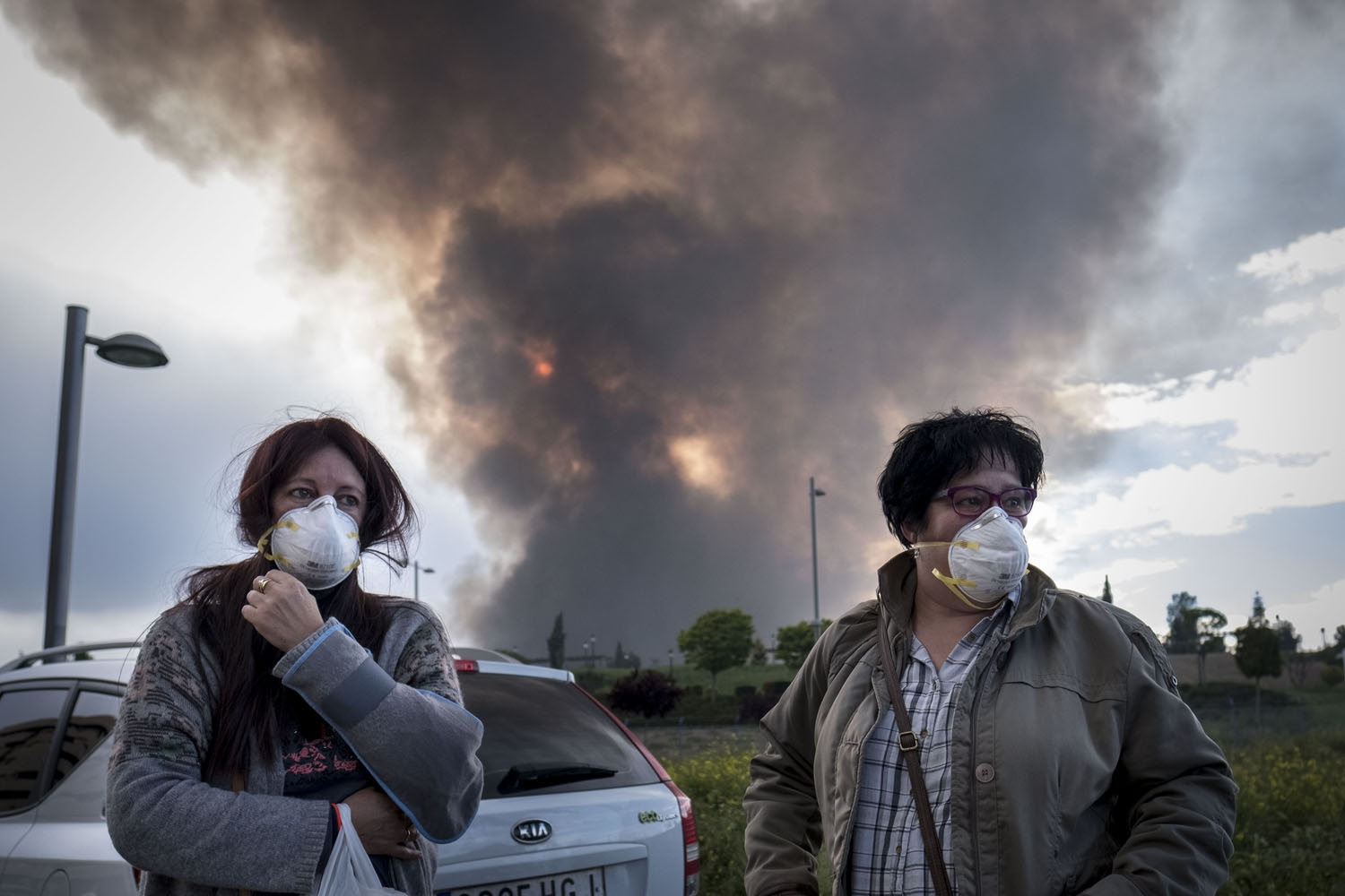 Two neighbours of Sesena wear masks as they wait for other relatives to evacuate a residential area affected by th toxic fumes produced by tyres burning in an uncontrolled dump