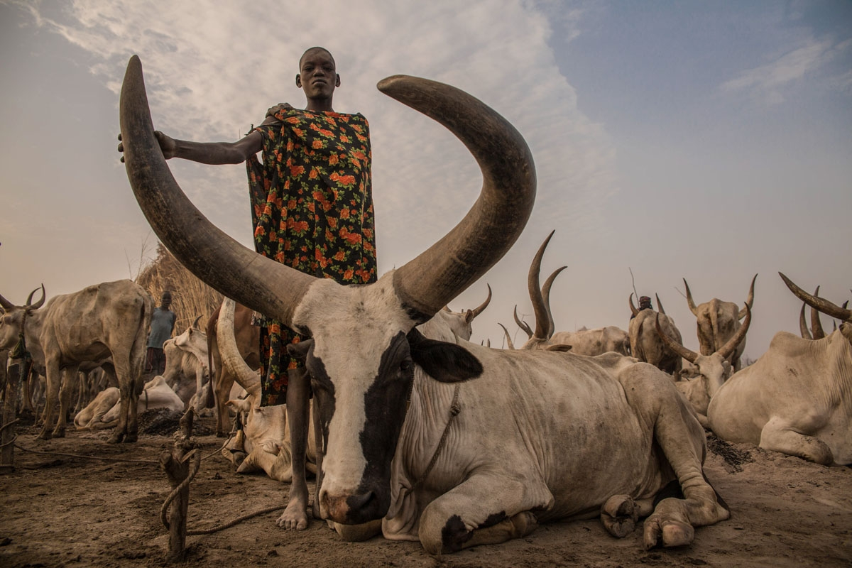 Sudanese girl Den, (14) from Dinka tribe who works as a cattle keeper, cook and cleaner and aid to her brother without attending any school poses at their cattle camp in Mingkaman, Lakes State, South Sudan on March 3, 2018. During South Sudan's dry sea