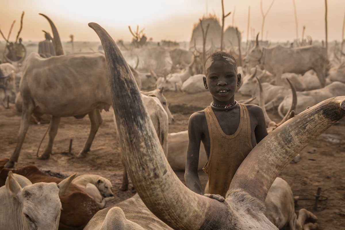 A Sudanese boy from Dinka tribe poses next to his cow at their cattle camp in Mingkaman, Lakes State, South Sudan, on March 3, 2018.