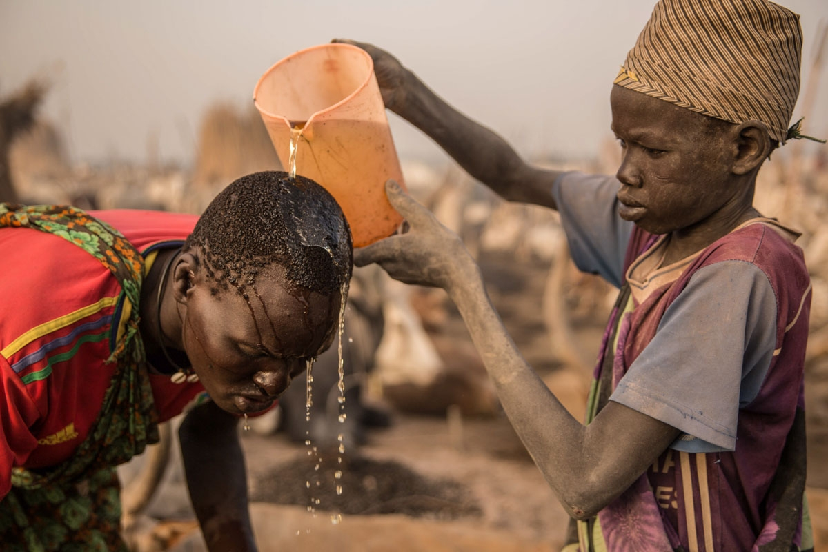 Sudanese boys from Dinka tribe use cow's urine to wash hair at their cattle camp in Mingkaman, Lakes State, South Sudan, on March 3, 2018. During South Sudan's dry season between December and May, pastoralists from the highlands move to the lowlands and