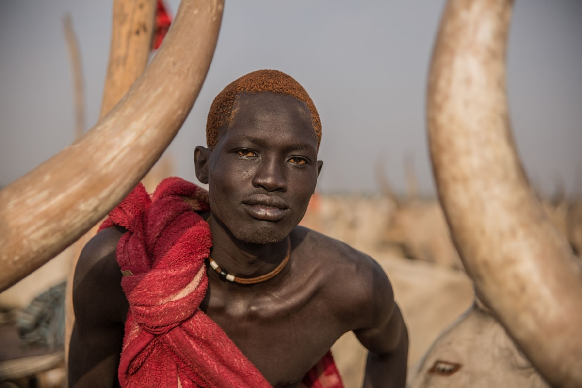 A Sudanese man from Dinka tribe shows his orange hair bleached by cow's urine at their cattle camp in Mingkaman, Lakes State, South Sudan, on March 3, 2018.