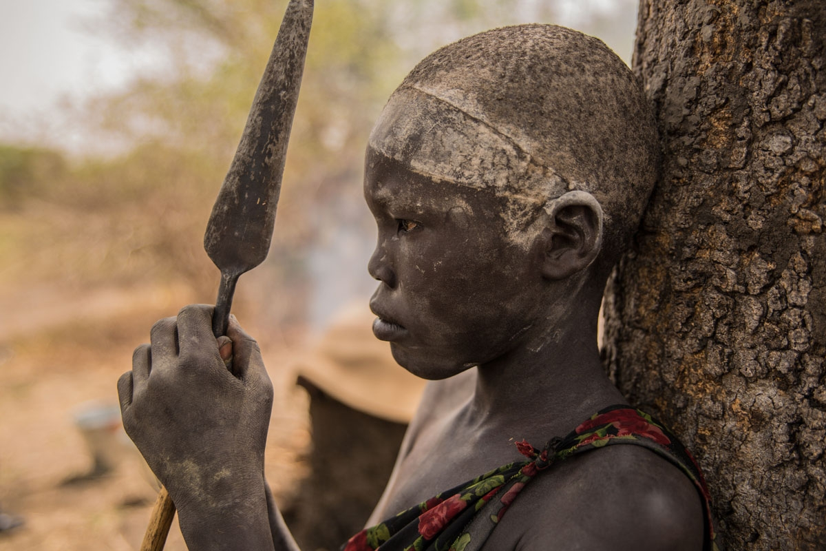 A Sudanese boy from Dinka tribe holds his spear at their cattle camp in Mingkaman, Lakes State, South Sudan on March 3, 2018.
