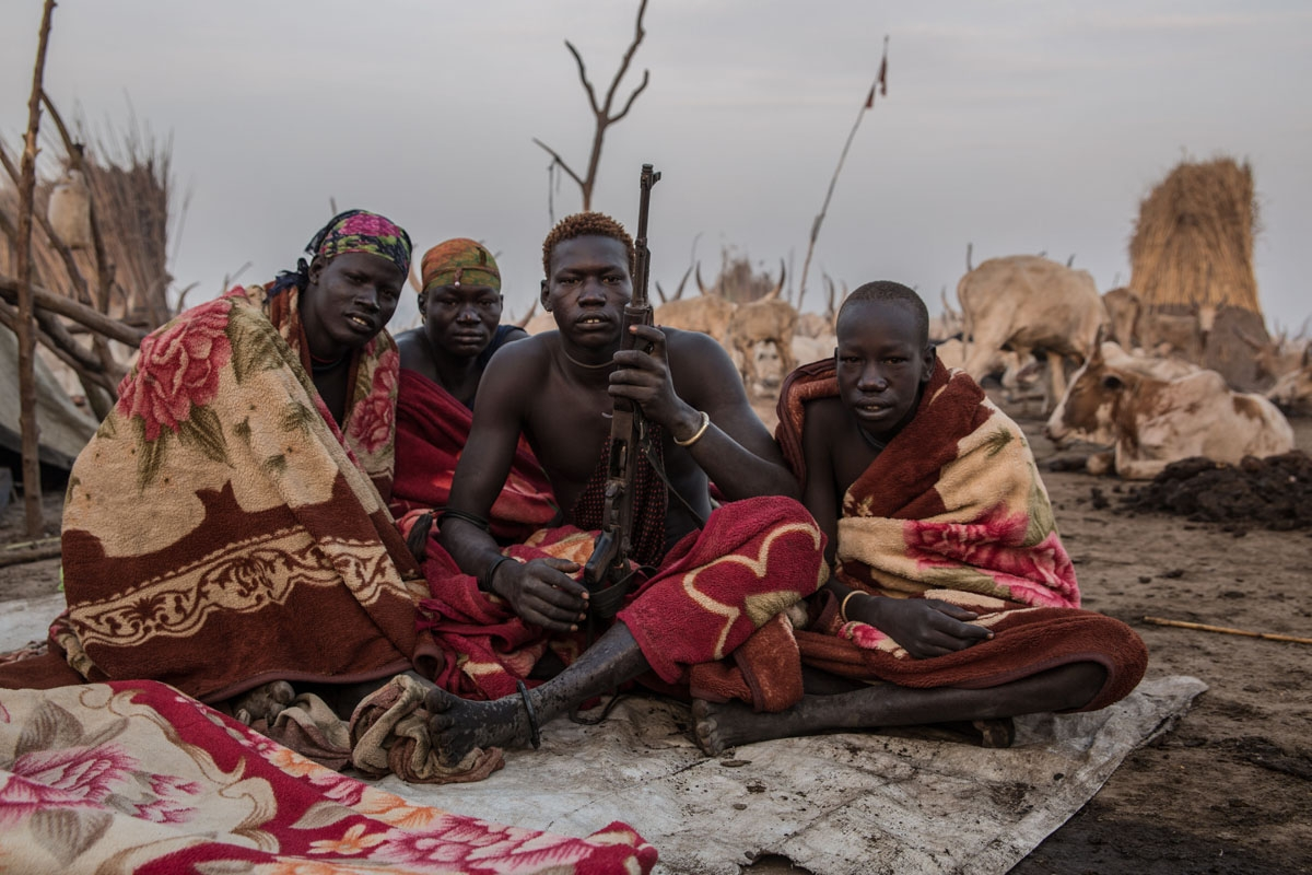 Sudanese men from Dinka tribe pose with a rifle in the early morning at their cattle camp in Mingkaman, Lakes State, South Sudan on March 4, 2018.
