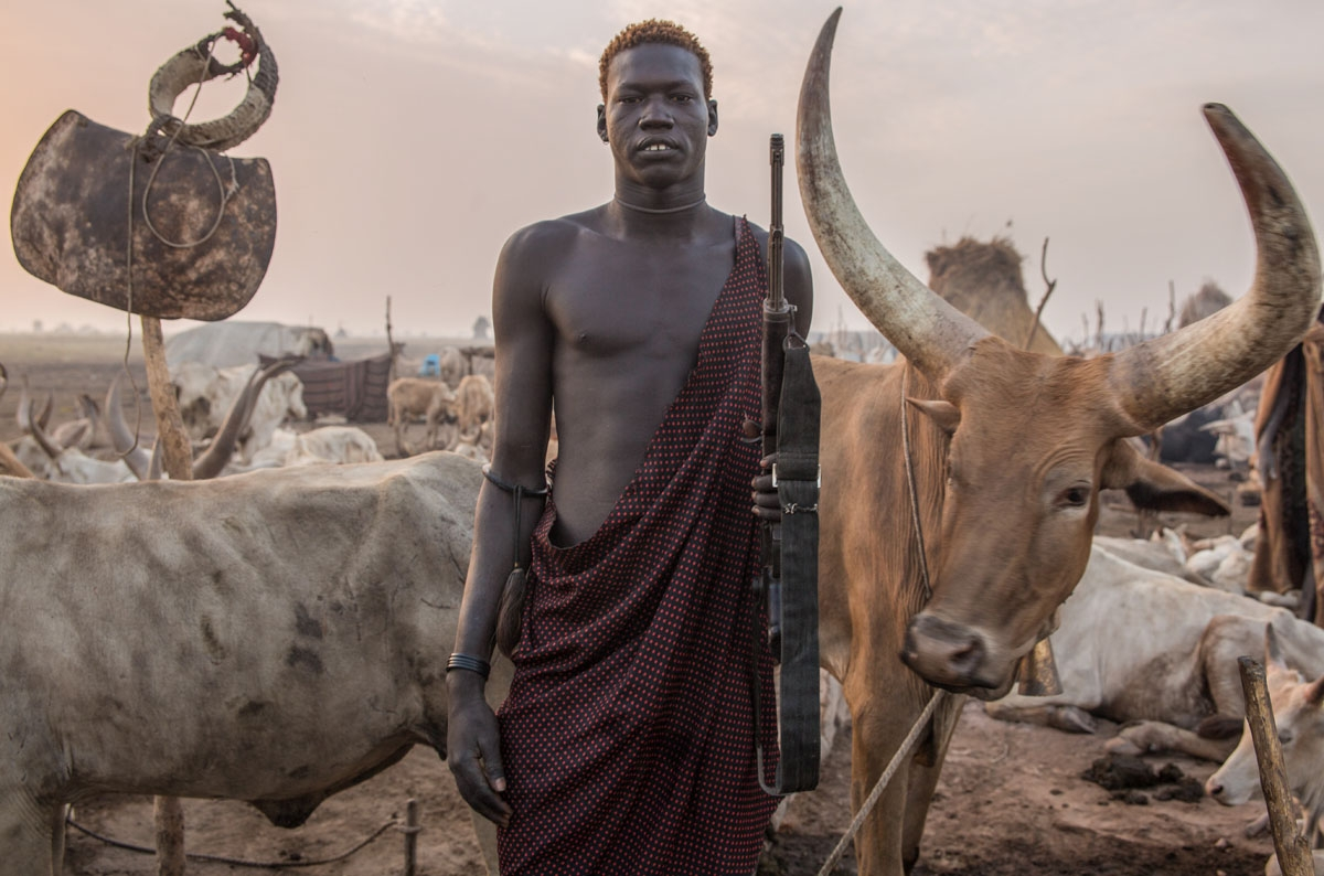 A Sudanese man from Dinka tribe poses with a rifle in the early morning at their cattle camp in Mingkaman, Lakes State, South Sudan on March 4, 2018.