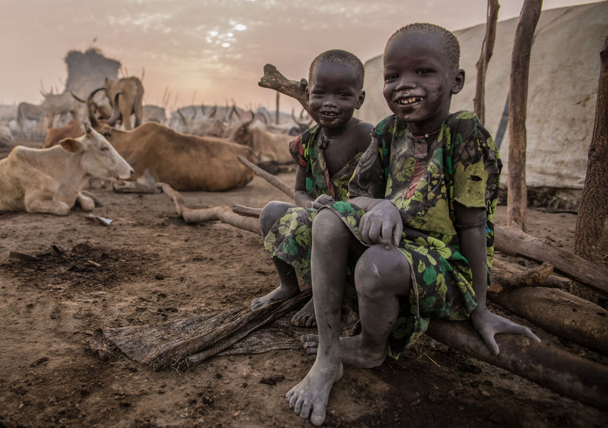 Sudanese boys from Dinka tribe pose in the early morning at their cattle camp in Mingkaman, Lakes State, South Sudan on March 4, 2018.