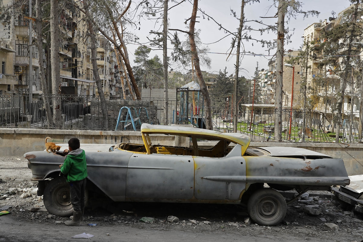 A picture taken on March 9, 2017, shows a boy playing with a cat next to a 1948 Buick parked outside the home of Mohammad Mohiedine Anis in the formerly rebel-held al-Shaar neighbourhood.