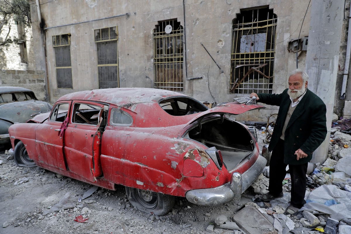 A picture taken on March 9, 2017, shows 70-year-old Mohammad Mohiedine Anis opening the trunk of his 1949 Hudson Commodor outside his home in Aleppo's formerly rebel-held al-Shaar neighbourhood.