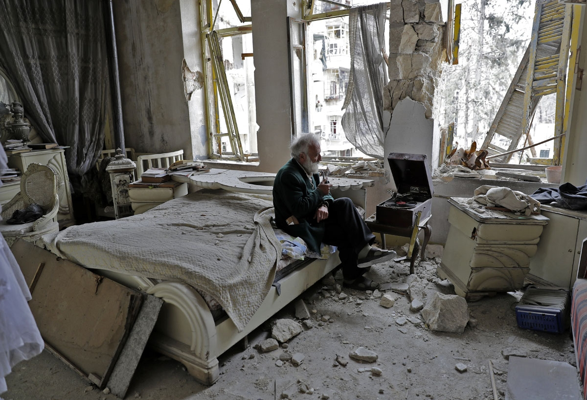 Mohammad Mohiedine Anis, 70, smokes his pipe as he sits in his destroyed bedroom listening to music on his vinyl player, gramophone, in Aleppo's formerly rebel-held al-Shaar neighbourhood.