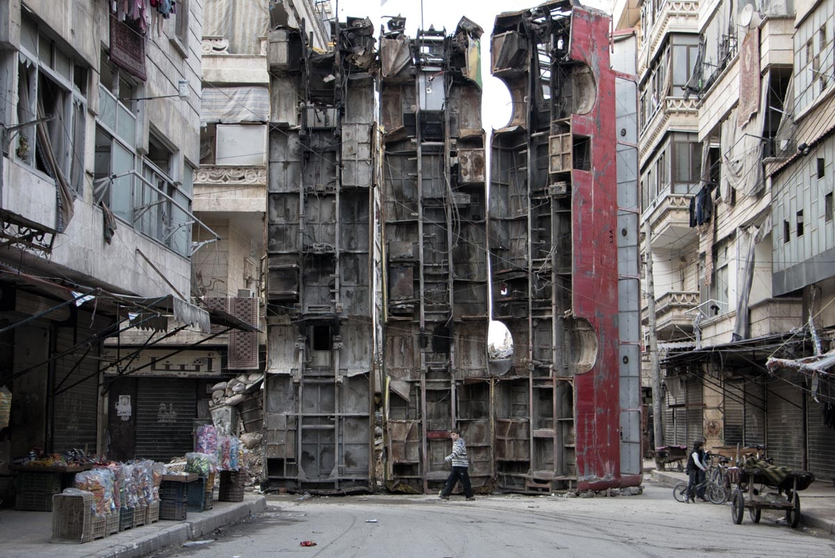 A young boy walks past a makeshift barricade made of wreckages of buses to obstruct the view of regime snipers and to keep people safe, on March 14, 2015 in the rebel-held side of the northern Syrian city of Aleppo. Syria's conflict enters its fifth year