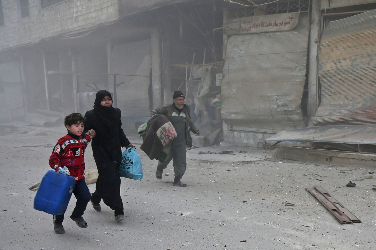 Syrians run for cover in Hammuriyeh following government shelling, March 6, 2018.
