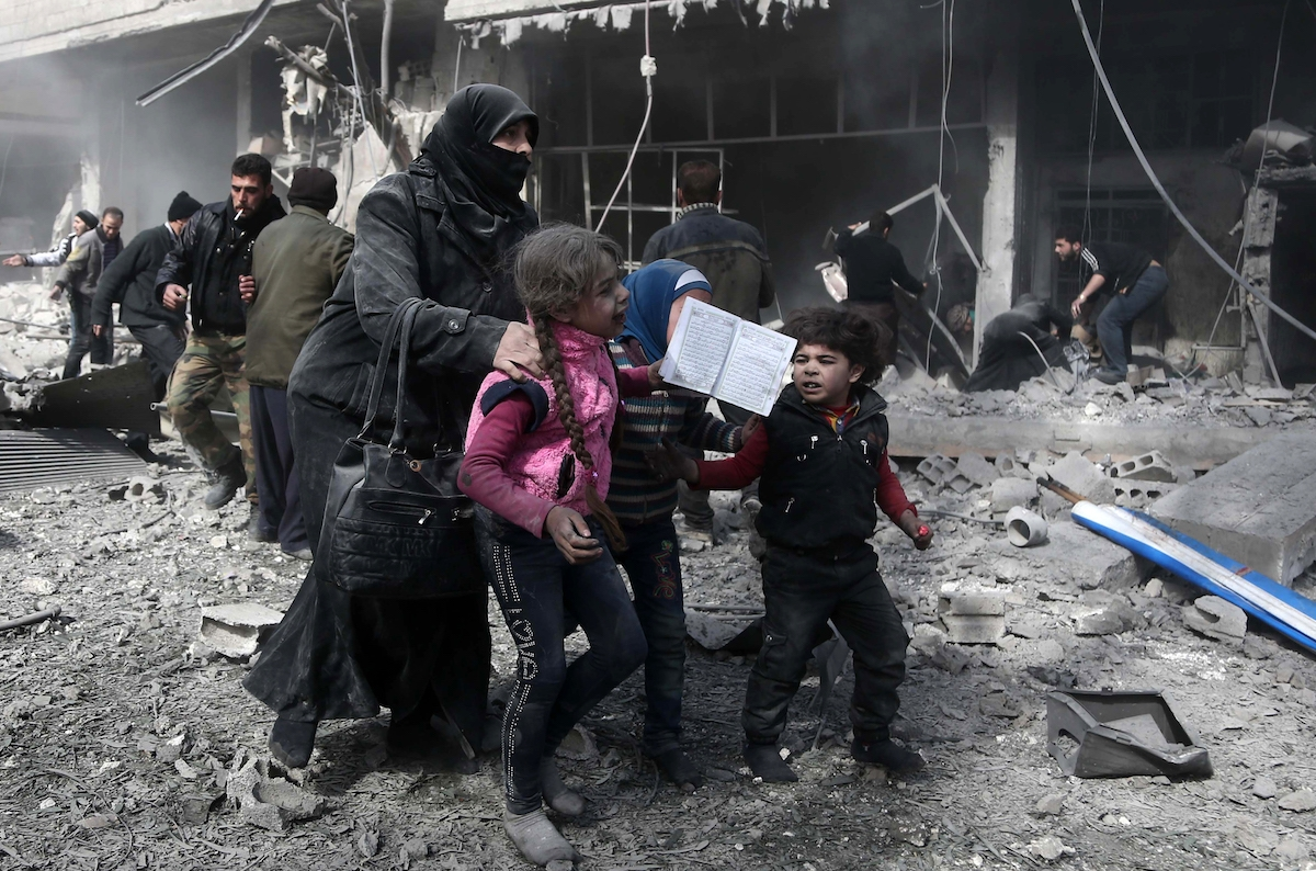 A Syrian woman and children run for cover amid the rubble of buildings following government bombing in the rebel-held town of Hamouria, in the besieged Eastern Ghouta region on the outskirts of the capital Damascus, on February 19, 2018.
