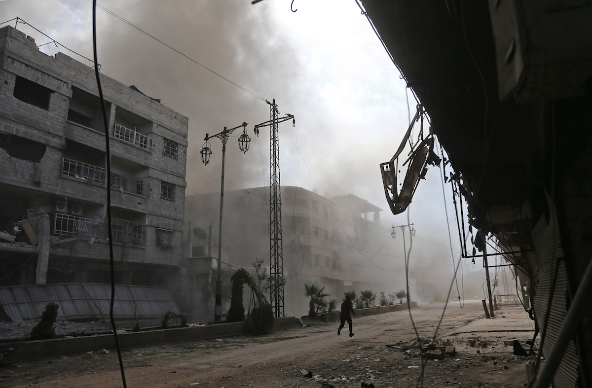 Smoke and dust are seen following a reported regime air strike in the rebel-held town of Hamouria, in the besieged Eastern Ghouta region on the outskirts of the capital Damascus on February 21, 2018.