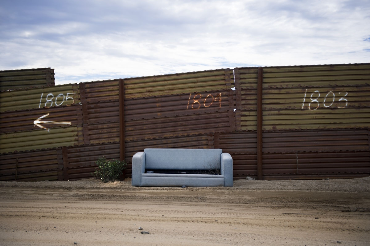 An abandoned sofa sits against the border fence on the US/Mexico border in Tecate, California on February 14, 2017.