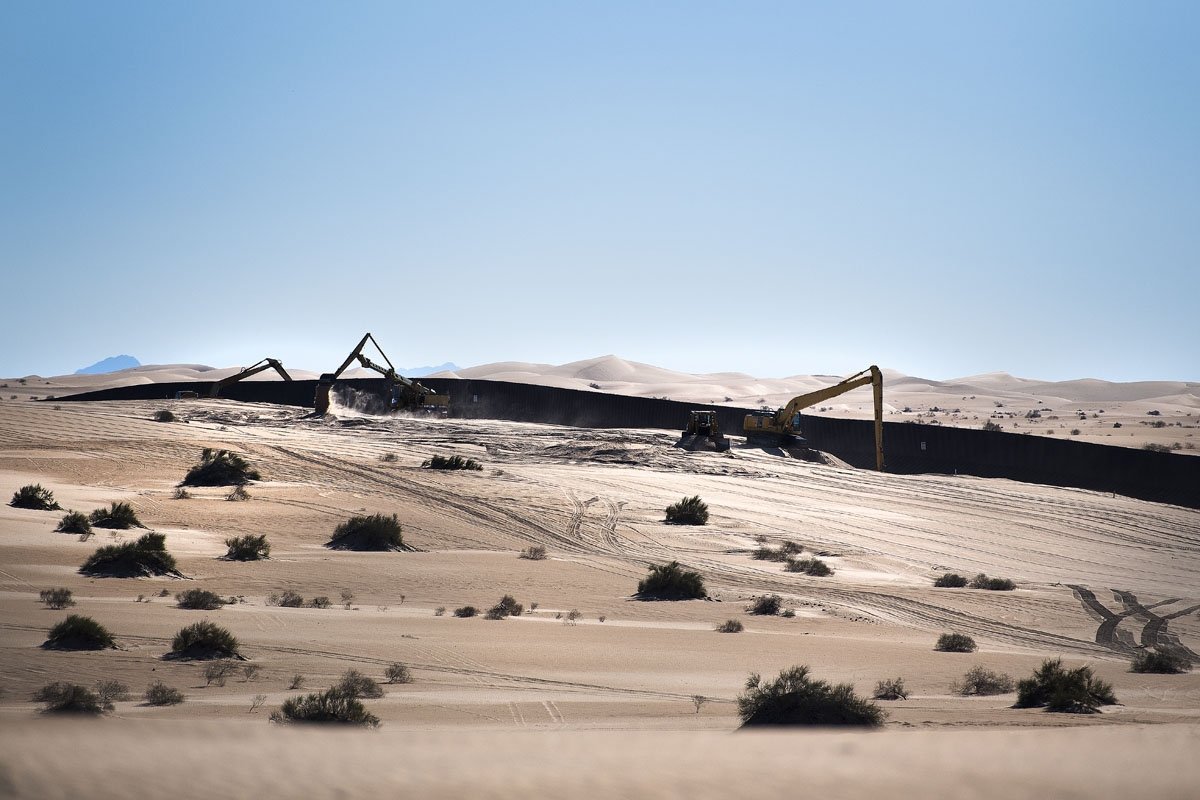 A construction crew works near the border fence on the US/Mexico border at the Imperial Sand Dunes in Dunes, CA, on February 15, 2017.