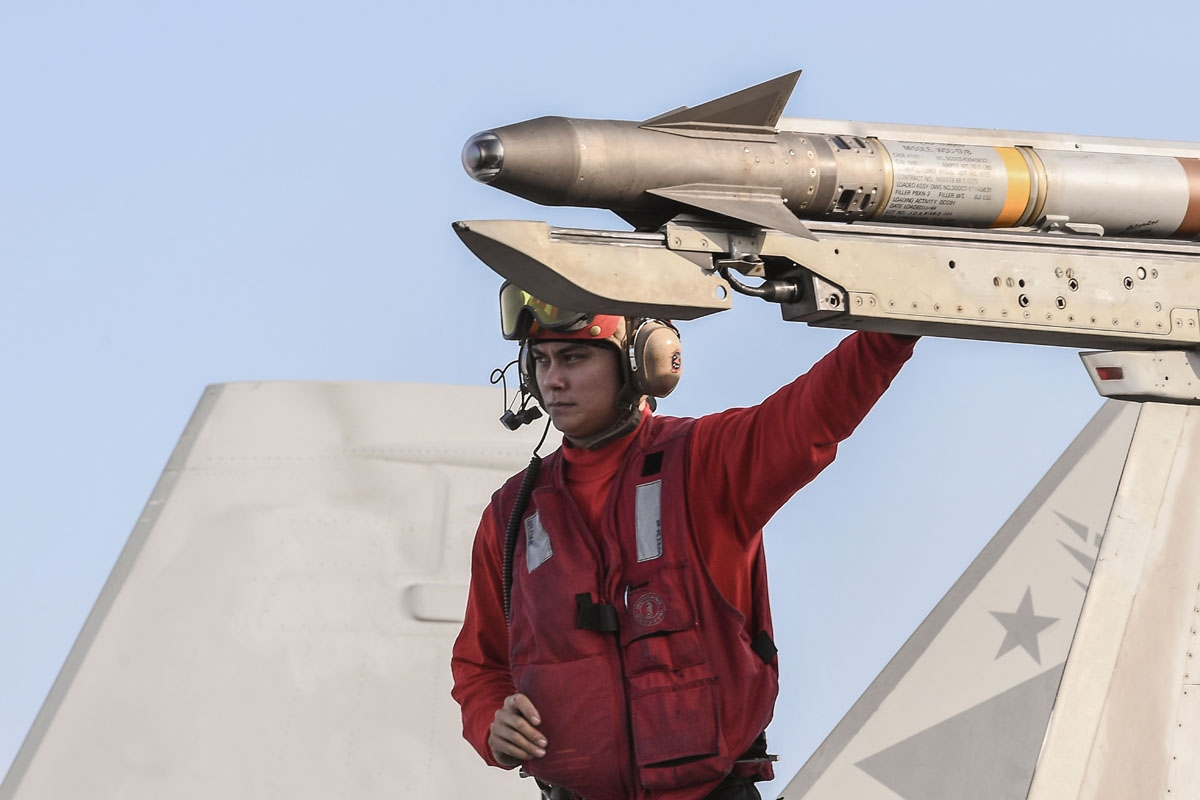 A crew member touches a missile on an F18 Hornet fighter jet stationed on the deck of the US navy aircraft carrier USS Harry S. Truman in the eastern Mediterranean Sea on May 8, 2018.