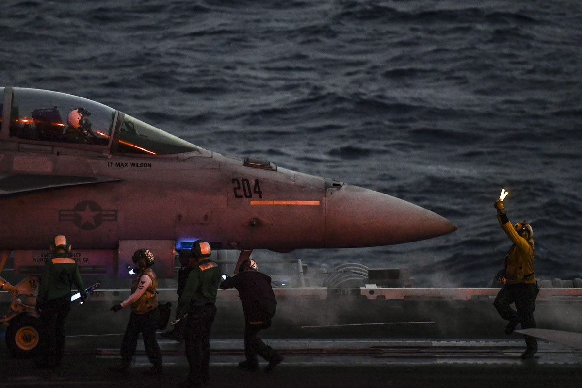 A crew member of the 330 meters US navy aircraft carrier Harry S. Truman gestures as a pilot of an F18 Hornet fighter jet waits to take off on eastern Mediterranean Sea on May 8, 2018.