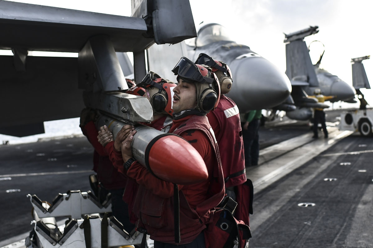 Crew members of US aircraft carrier USS Harry S Truman lift a missile into place on the wing of an F18 Hornet fighter jet on the flight deck of the ship in the eastern Mediterranean Sea on May 8, 2018.