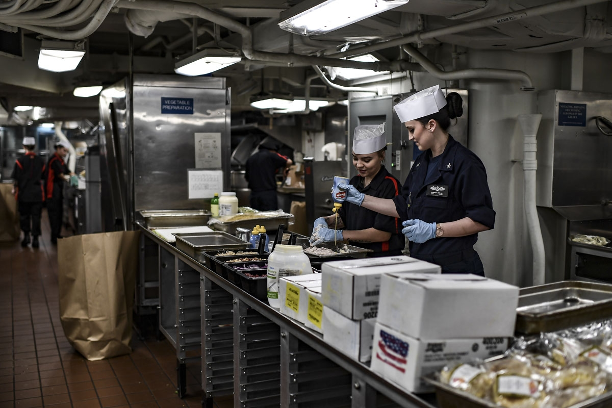 Crew members of the 330 meters aircraft US carrier Harry S Truman prepare meals in the kitchen of the warship on eastern Mediterranean Sea on May 8, 2018.