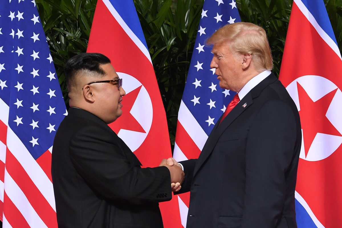 North Korea's leader Kim Jong Un (L) shakes hands with US President Donald Trump (R) at the start of their historic US-North Korea summit, at the Capella Hotel on Sentosa island in Singapore on June 12, 2018.