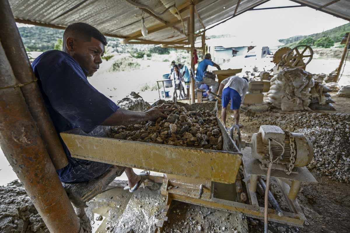 A man works at a stone crusher machine in a gold mine in El Callao, Bolivar state, southeastern Venezuela on February 25, 2017. Although life in the mines of eastern Venezuela is hard and dangerous, tens of thousands from all over the country head for the