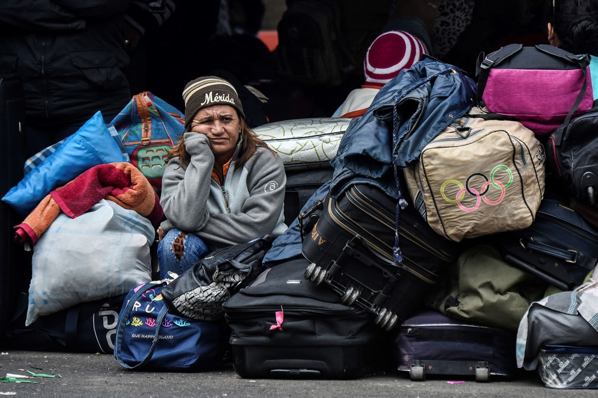 A Venezuelan woman waits outside the Colombian migration office near the Rumichaca bridge before crossing into Ecuador, August 20, 2018.