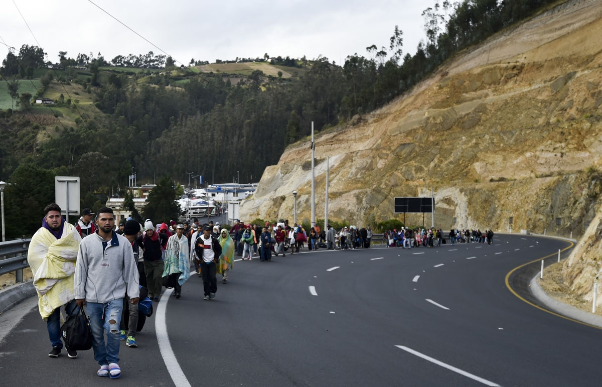 Venezuelans heading to Peru walk along the Panamerican highway in Tulcan, Ecuador, after crossing from Colombia, on August 21, 2018.