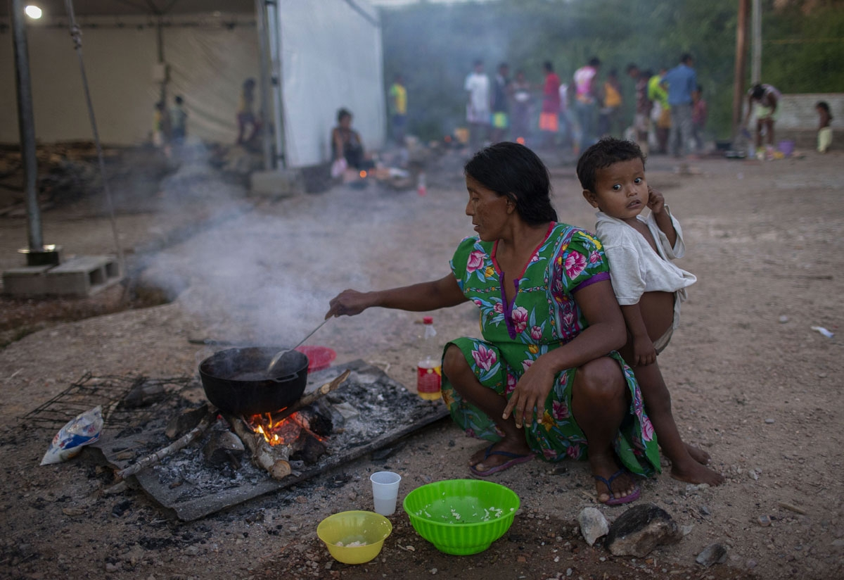 Members of the Warao tribe, Venezuela's second-largest indigenous group, prepare food at the Janokoida shelter where they have been taking refuge in the border city of Pacaraima, Roraima State, Brazil, on August 21, 2018.