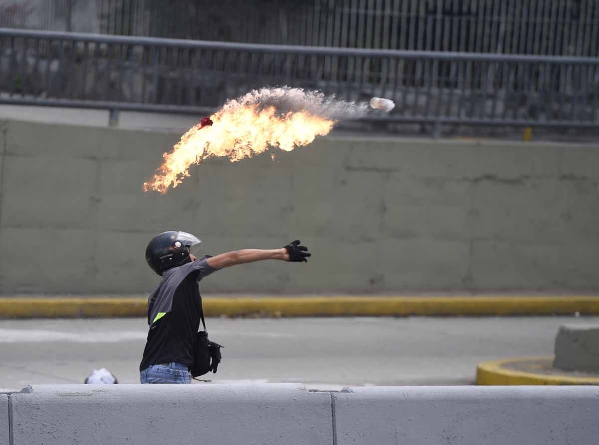 A demonstrator against Nicolas Maduro's government throws a Molotov cocktail during clashes with riot police at eastern Caracas on April 8, 2017.
