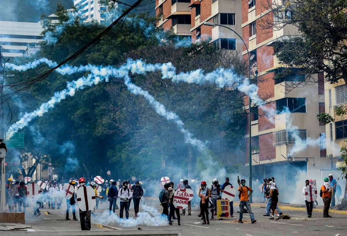Opposition demonstrators and riot police clash during a protest against Venezuelan President Nicolas Maduro, in Caracas on May 3, 2017. Venezuelan police fired tear gas and hooded protesters hurled Molotov cocktails as thousands rallied Wednesday in anger