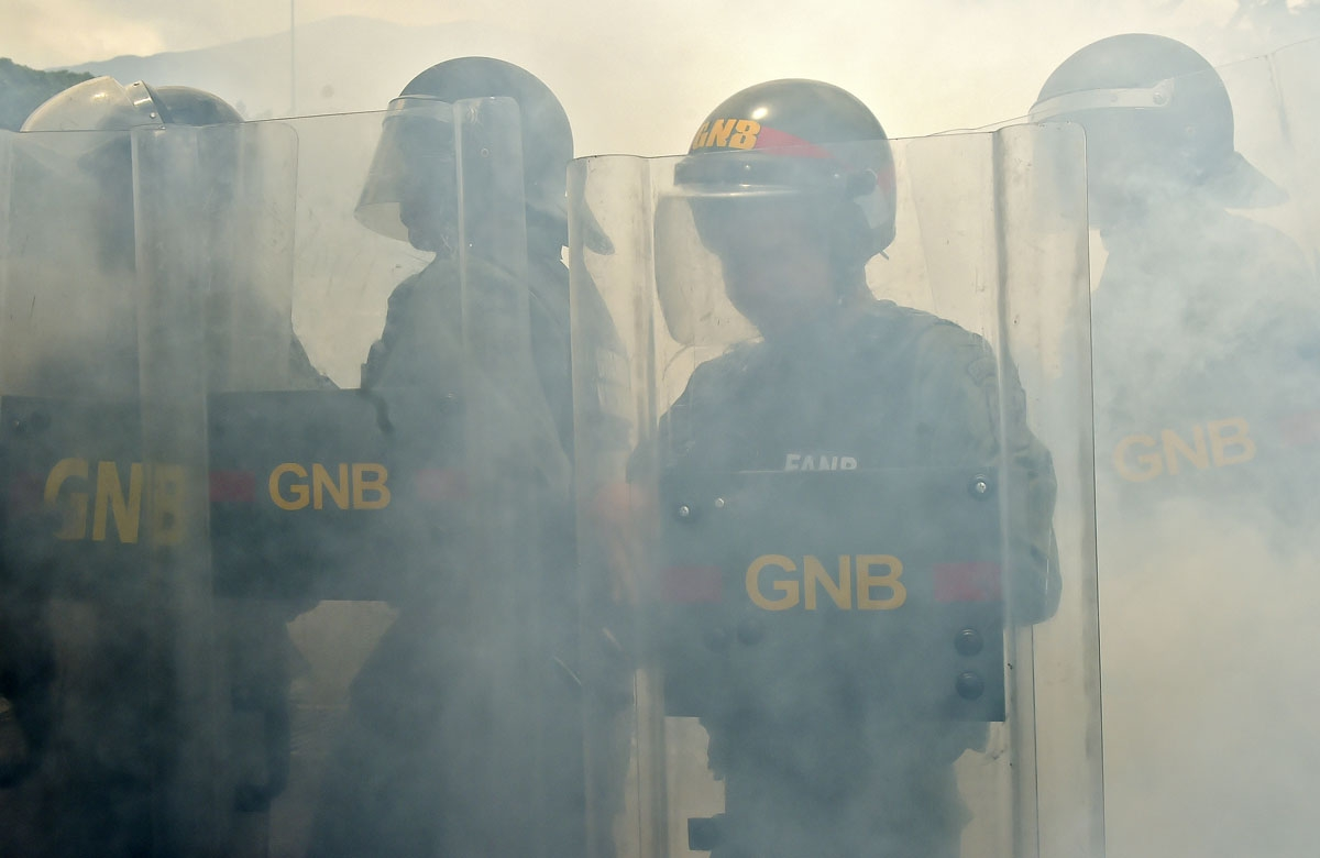 Members of the National Guard crack down on opposition demonstrators during a march against President Nicolas Maduro, in Caracas on April 26, 2017.  Venezuelan riot police fired tear gas to stop anti-government protesters from marching on central Caracas,