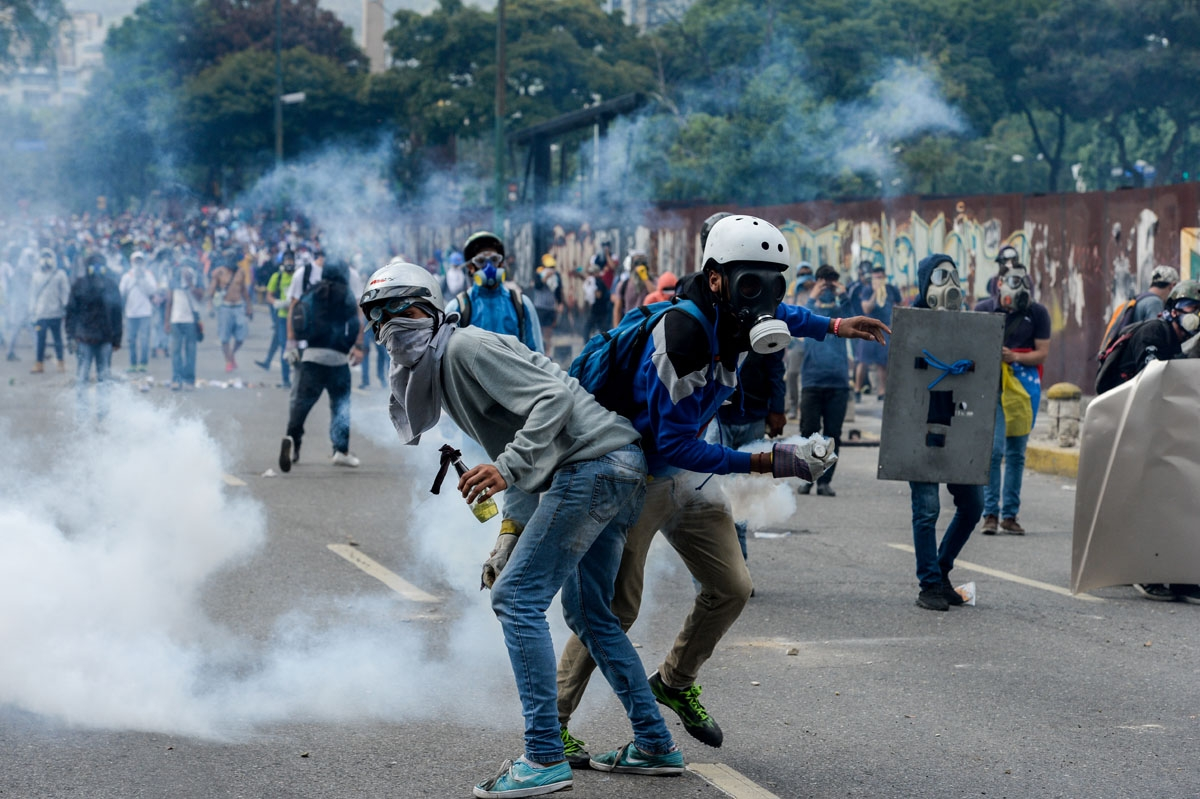 Opposition activists clash with riot police during a protest against President Nicolas Maduro in Caracas on April 26, 2017.
