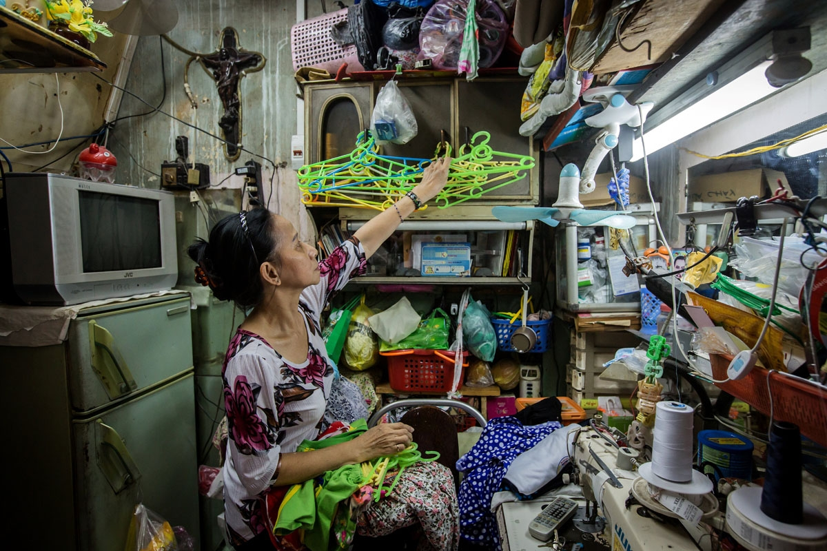 Nguyen Thi Kim Ngoc arranges cloth-hangers in her 6.7-square-metre home in Ho Chi Minh City on May 3, 2018.