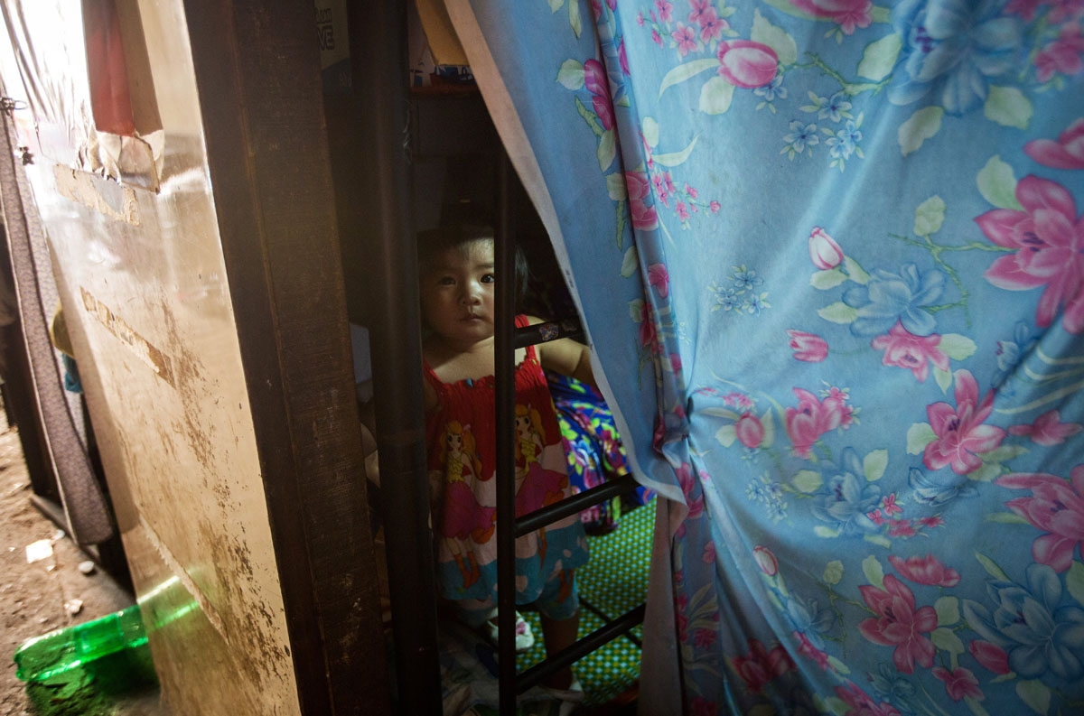 A girl looks out from her uncle's two-square-metre home in Ho Chi Minh City on May 2, 2018.