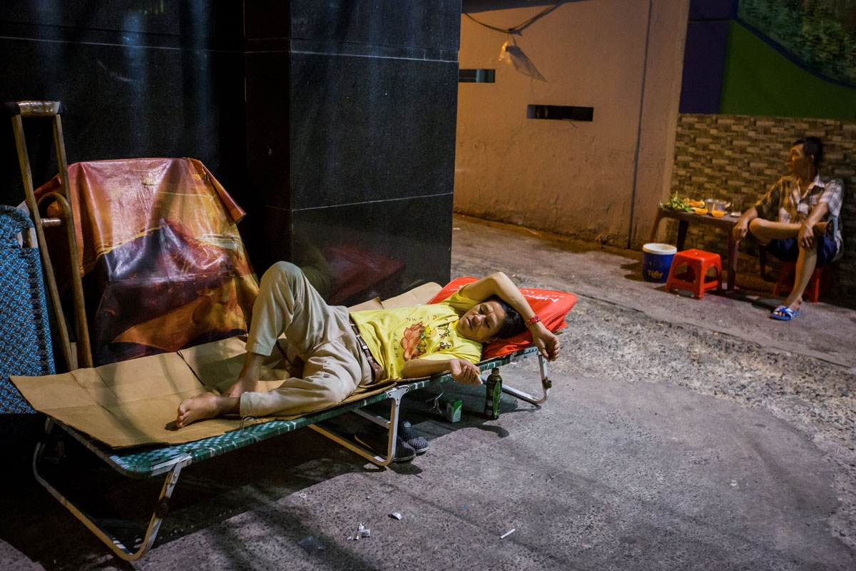 Pham Quoc Cong rests on a makeshift bed outside his two-square-metre home in Ho Chi Minh City on May 2, 2018.