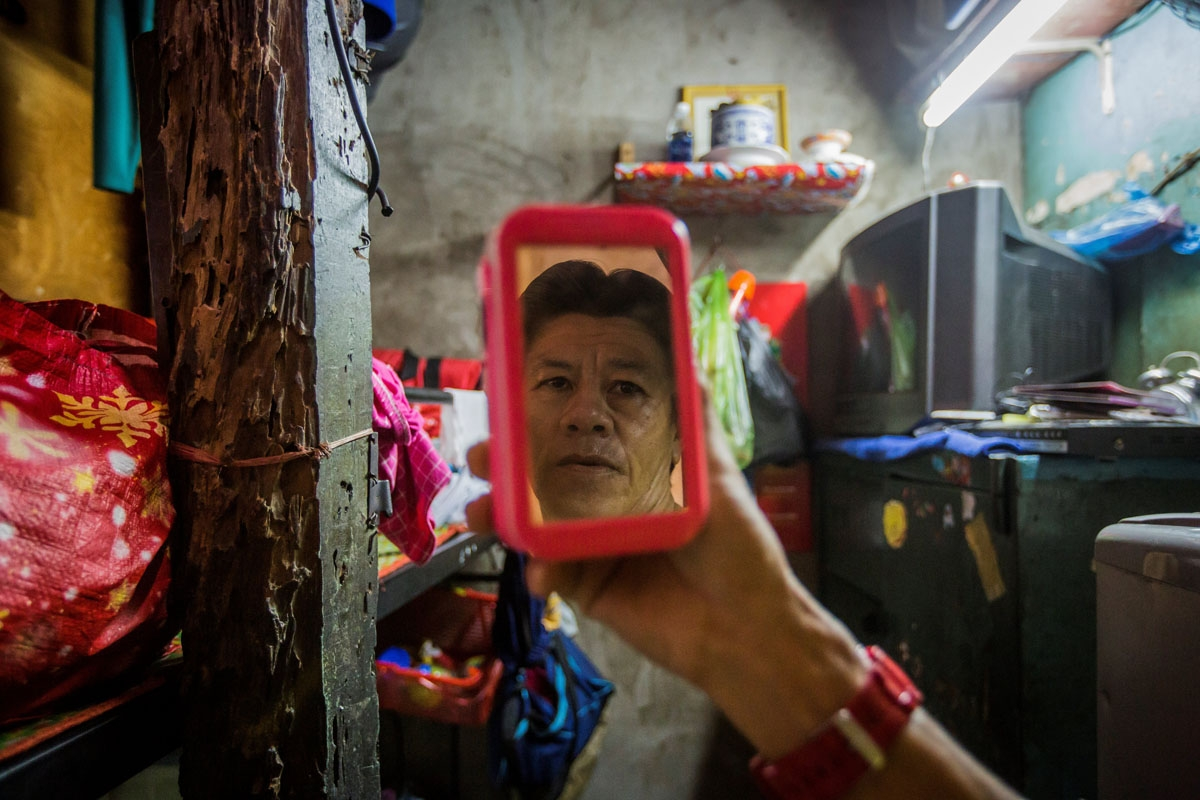 Pham Quoc Cong poses inside his two-square-metre home in Ho Chi Minh City on May 2, 2018.