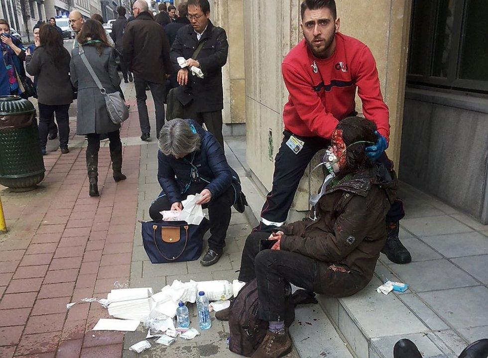 Un guardia de seguridad ayuda a una mujer herida fuera de la estación de Maalbeek, en Bruselas, el 22 de marzo de 2016